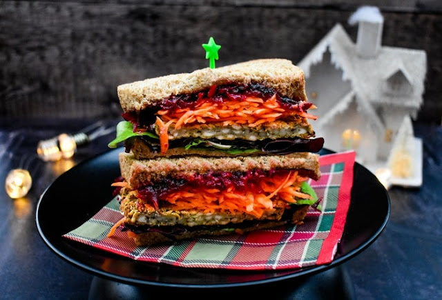 A Christmas Feast Sandwich Stacked on a black plate with a tartan napkin. Christmas lights in the background.