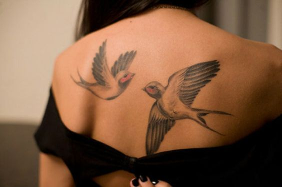Mujer katina de espaldas con vestido de noche, dos palomas tatuadas entre sus omoplatos