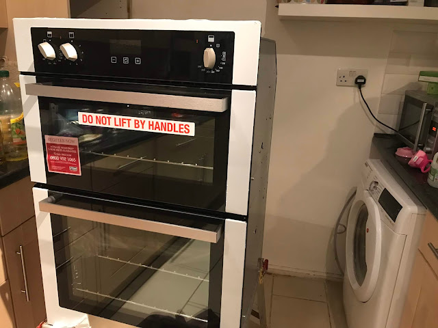 A photo taken mid installation of the oven showing the oven on a stand ready to be connected