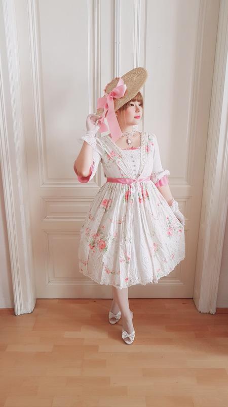 woman wearing a yolanda lolita dress and a bergere hat with a pink ribbon