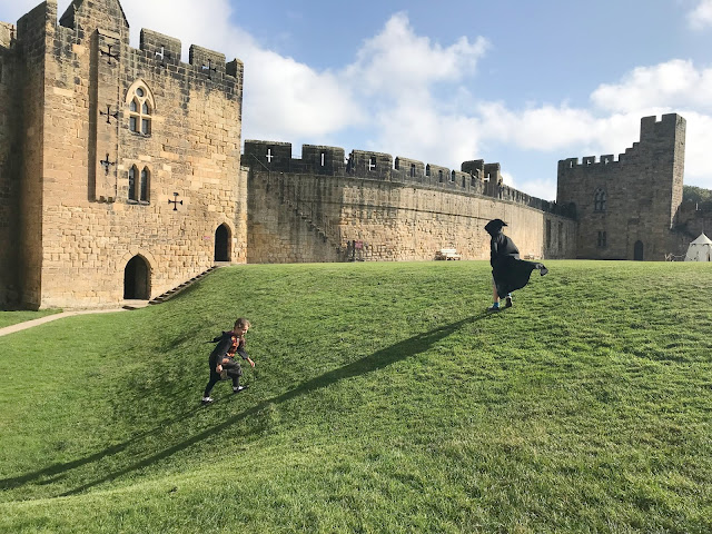 children at alnwick castle walking outside on the grass