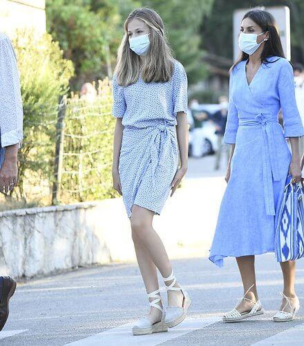 Queen Letizia wore a blue midi linen wrap dress by Adolfo Dominguez. Crown Princess Leonor wore a knot detail mini dress by Other Stories