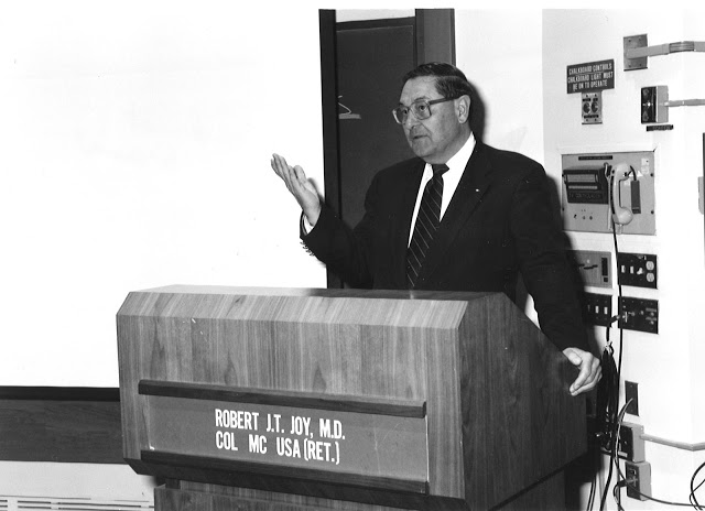 Dr. Robert J.T. Joy speaks at a podium.