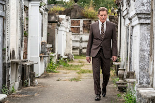 Bryan Cranston in a suit walking through a graveyard