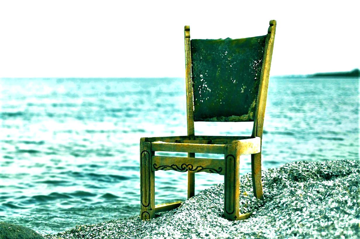 old chair on rocks overlooking ocean