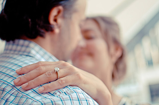 A man and woman in soft focus, with a close-up of the woman's hand showing off her ring.