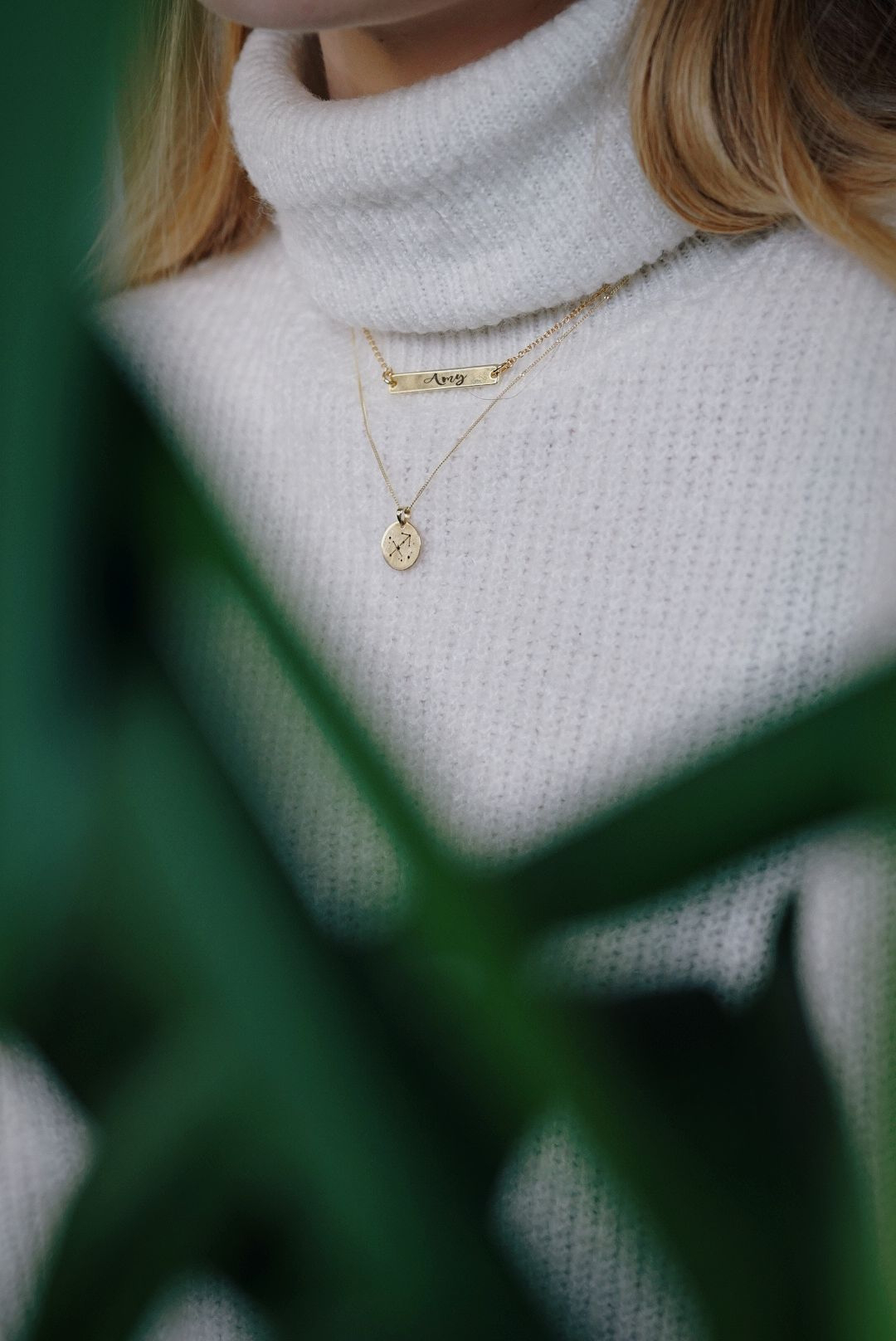 close up of girl wearing two necklaces, one is a gold bar necklace, the other a pendant