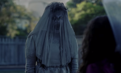"Movie still for the 2019 Paramount Pictures horror film ""The Curse of La Llorona"" where Marisol Ramirez as the Weeping Widow stares and screams at a child while wearing a white wedding gown"