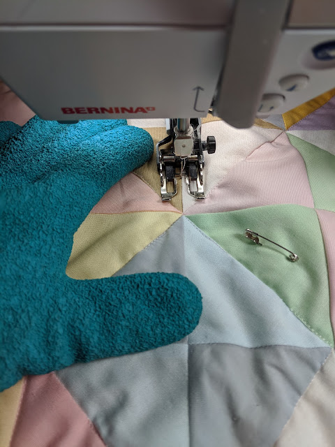 New rubberized, turquoise gardening gloves allow better control while machine quilting on a domestic machine.