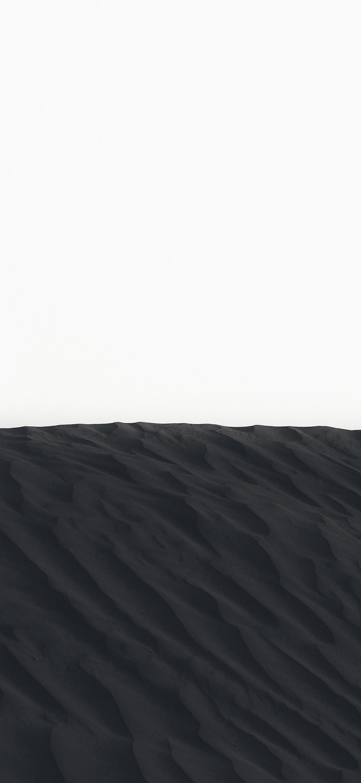 خلفية تلال الرمال السوداء تحت السماء البيضاء