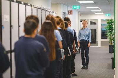 Elever står på rad i korridoren framför sin lärare.