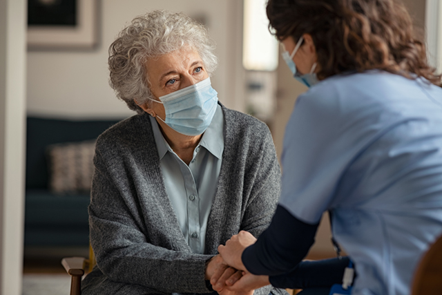 Woman in a care home being consoled by a member of staff