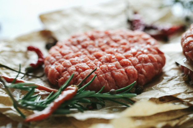 raw-beef-hamburger-patties-with-herbs-spices-dark-slate