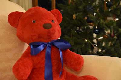 Red teddy bear next to Christmas tree