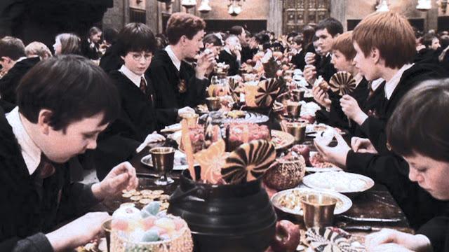escena en el gran comedor en la mesa destacan calderos llenos de piruletas y en la mesa vemos manzanas y otras frutas