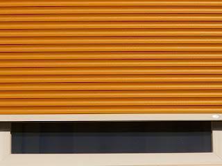 Un volet roulant orange presque totalement baissé, devant une fenêtre.