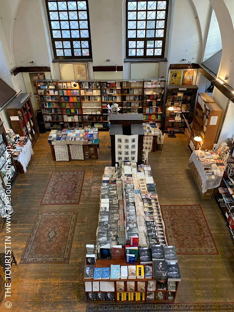 Bookshelves and tables with books in a large vaulted room with large windows on all sides..