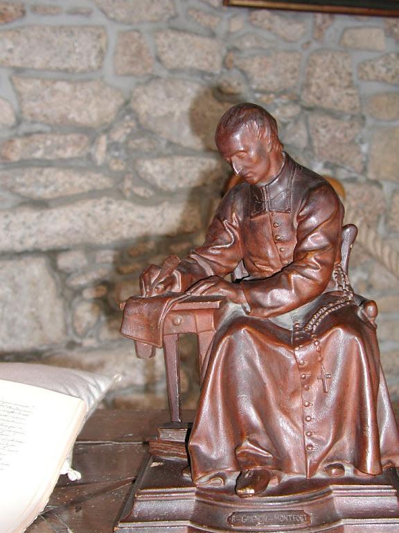 Estatueta representa ao Santo escrevendo o Tratado  sobre a escrivaninha que ele usou. St-Laurent-sur Sèvre