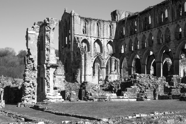 Monochrome photo of the main building at the top of the site. Two walls remain with lots of arched windows.