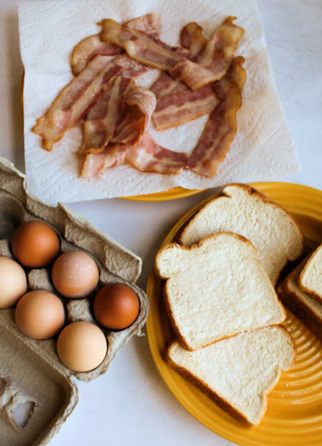 plate of partially cooked bacon, brown eggs and slices of bread ready to be assembled