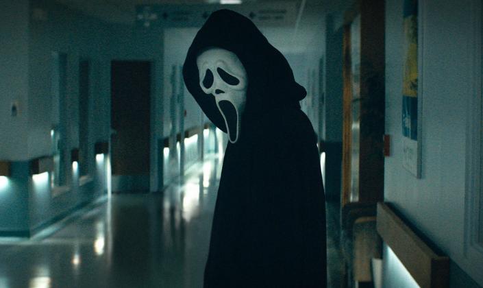 Imagem de capa: o assassino Ghostface de Pânico com uma máscara de fantasma com a boca aberta e preta e olhos como que chorando e numa fantasia preta com capuz, em um corredor de um hospital.