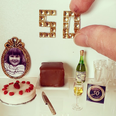 Modern dolls' house miniature 50th birthday scene with cake, champagne and a gold diamante '50' on the wall.