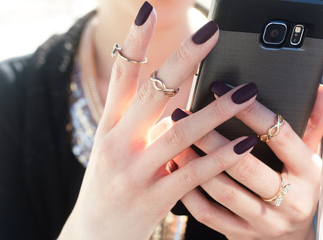 Close up of a woman's manicured hands and the rings she's wearing.