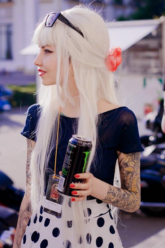 Chica de pelo largo blanco, esta paeando con una bebida, lleva tatuajes en el brazo izquierdo