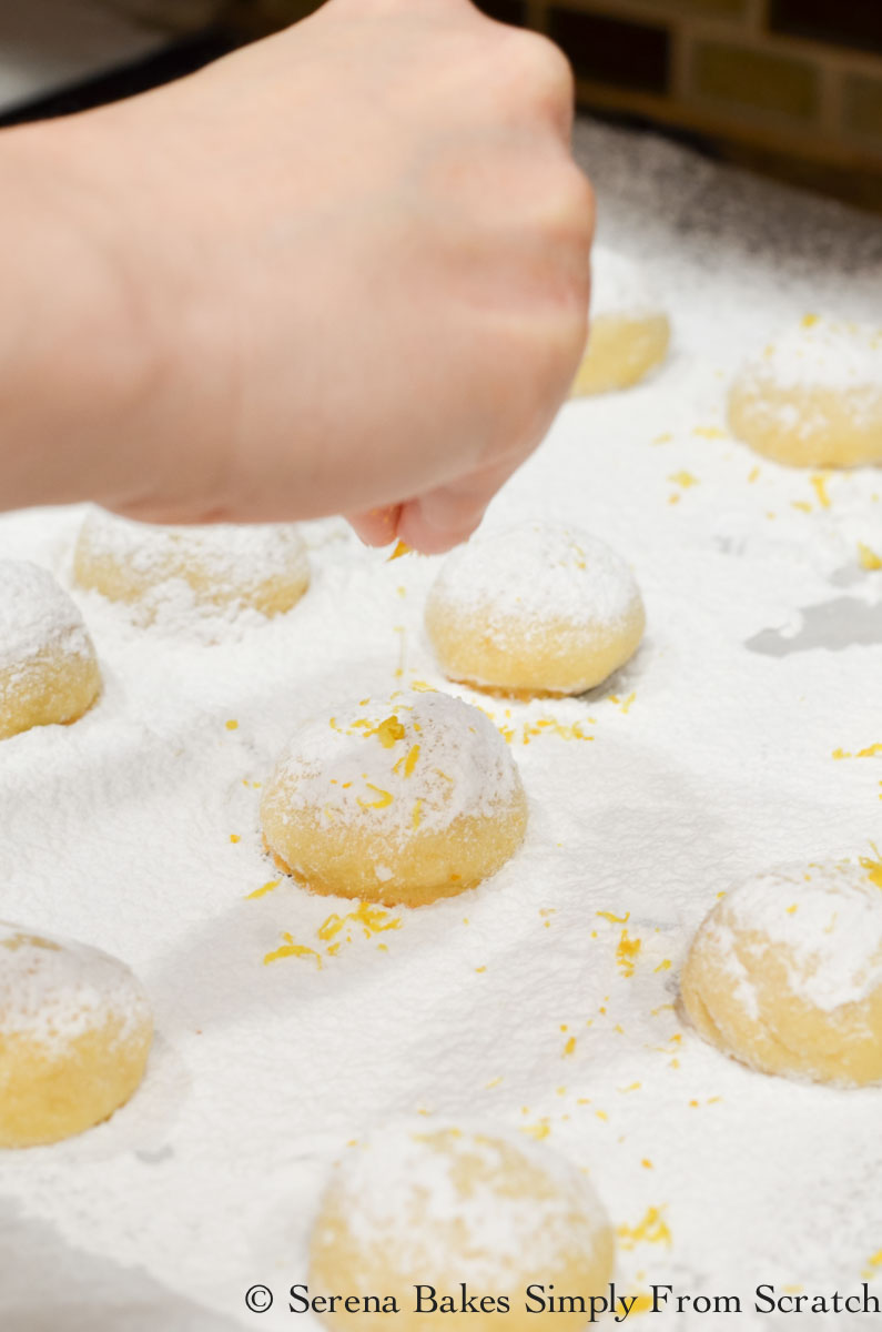 Lemon Snowball Cookies dusted with powdered sugar and topped with lemon zest.