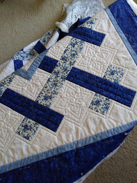 Quilting partially completed on blue and white patchwork quilt