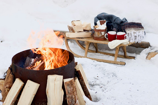Outside fireplace with old sled beside it at Mount Engadine Lodge