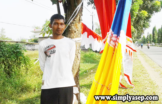 JUALAN : Kang Nano berjualan bendera berpindah pindah . Bergaya ditempat lokasi usahanya.  Foto Asep Haryono