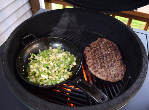 Flank steak, onions, and peppers cooking on a Big Green Egg.