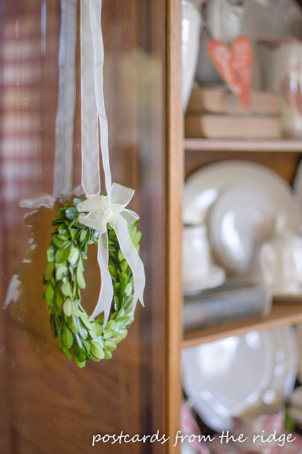 Cute little boxwood wreath on the hutch door.
