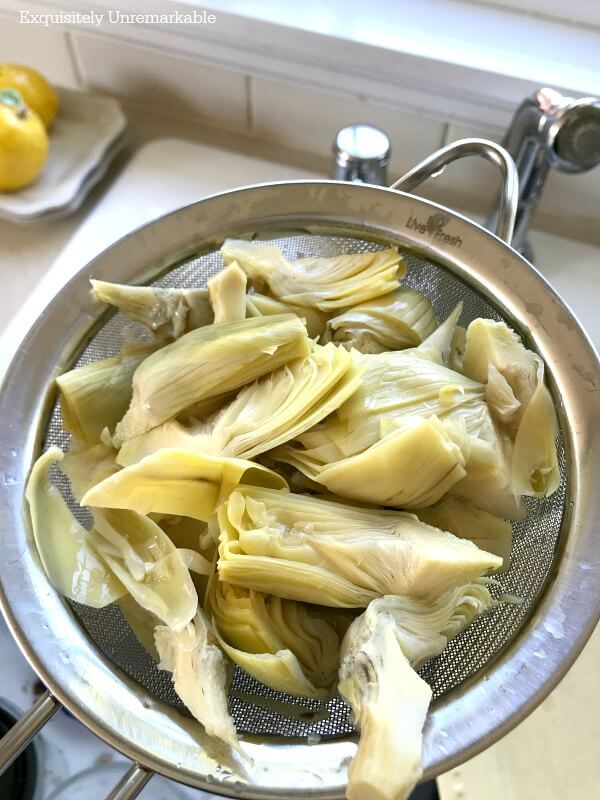 Rinsing Artichoke Hearts in a metal strainer