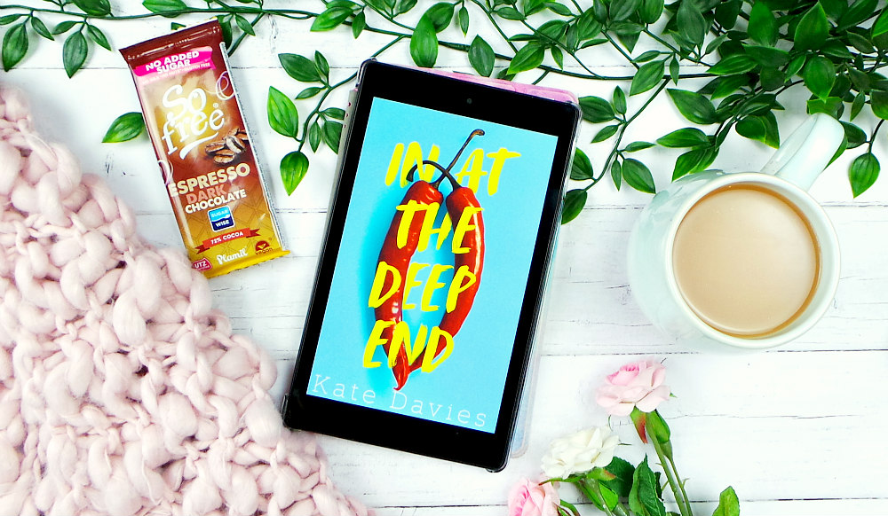 Kindle fire showing the In At The Deep End by Kate Davies cover. Theres leaves, a pink blanket and roses in the background