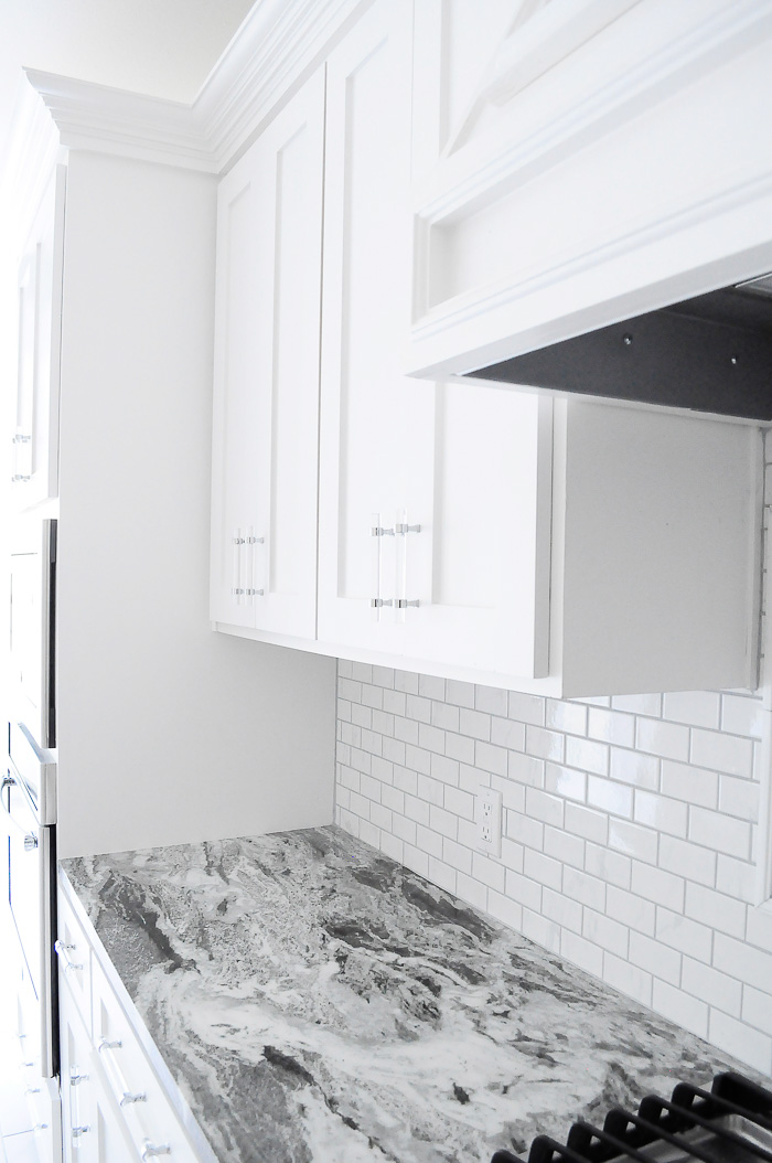 White shaker kitchen cabinets with thassos diamond reflection mirror tile as an accent. | via monicawantsit.com