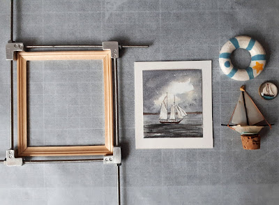 Flat lay of a 1/12 scale miniature frame in a jig, next to a grey watercolour of a boat, on a piece of card, next to a 1/12 scale model yacht, round picture of a yacht and a blue and white lifebuoy.