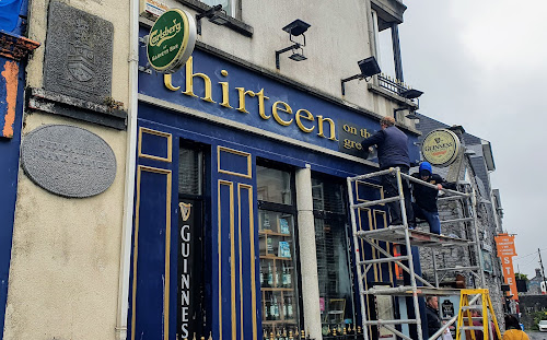 Workermen installing new signs saying 13-on-the-green in Garvey's Inn hotel in Eyre Square, Galway
