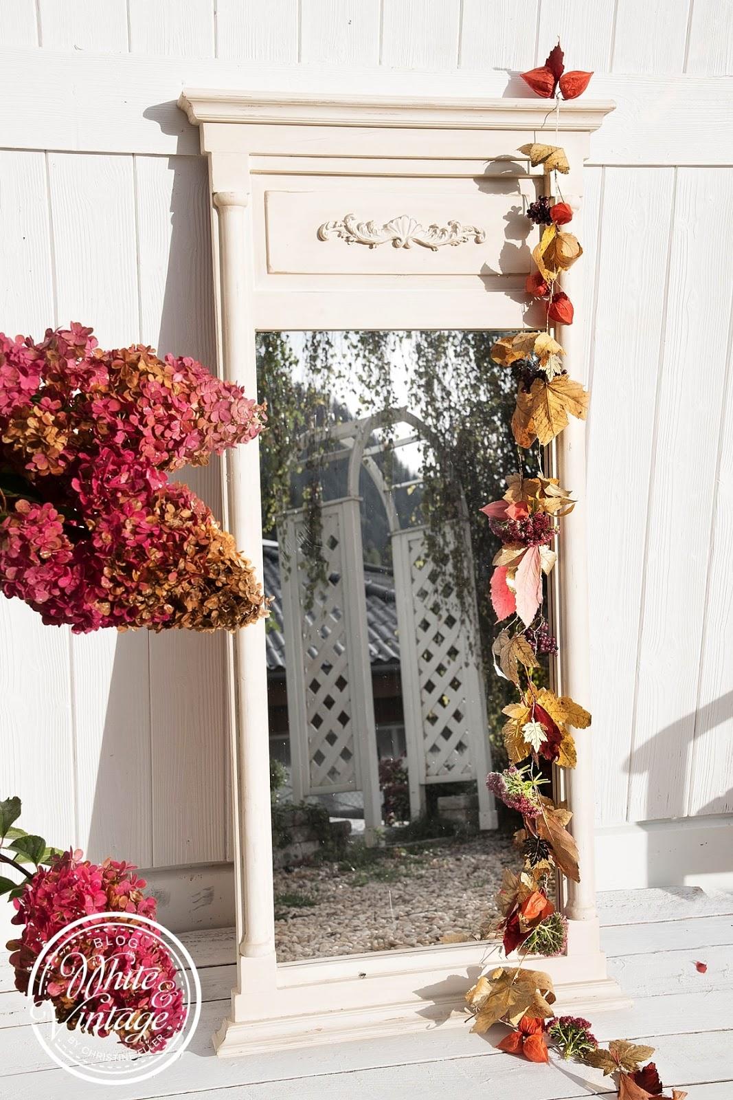 Spiegel mit Blättergirlande dekorieren.