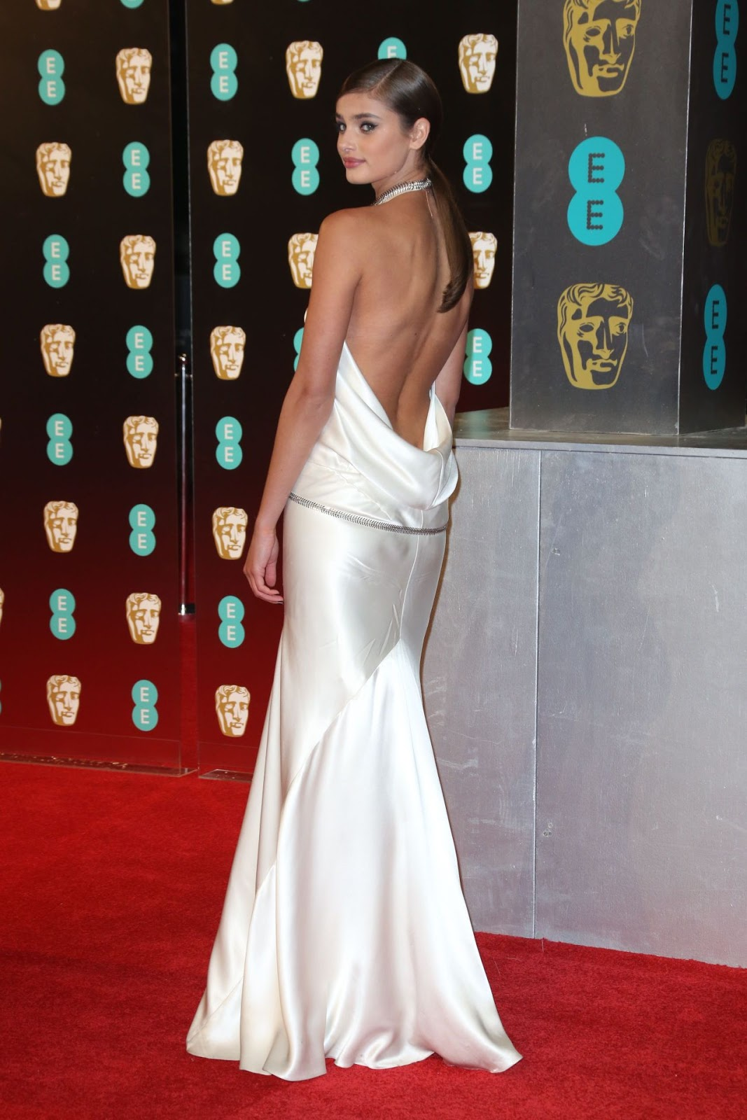 Taylor Hill flashed some serious skin in a white satin gown with a metal chain as she hit the BAFTAs at London's Royal Albert Hall