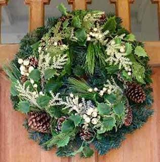 Door wreath with pinecones and white flowers.
