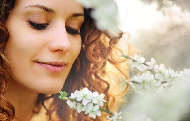 Donna allergica ai pollini che annusa un fiore