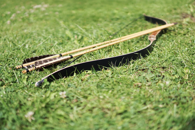 Bow and arrows on grass, archery