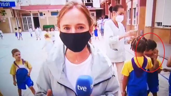 Reportera informa sobre la vuelta al cole sin besos ni abrazos mientras unos niños detras se besan y abrazan.