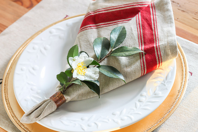 silver, gold and red with place setting with a camellia tucked in.