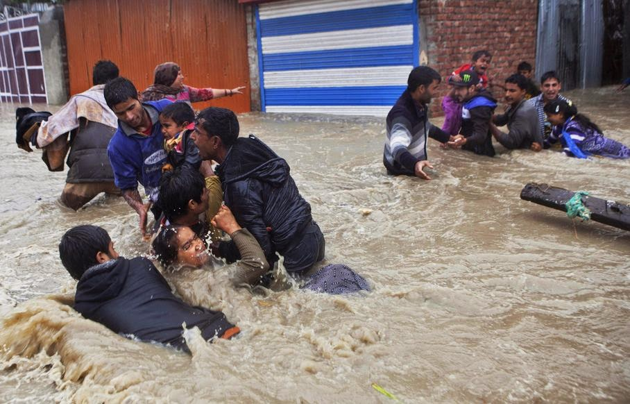 Kashmiri residents wade through floodwaters in Srinagar, India, Thursday, Sept. 4, 2014. At least 100 villages across the Kashmir valley were flooded by overflowing lakes and rivers.