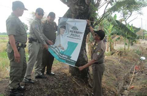 sejumlah atribut pilkada di astanajapura dipaku di pohon