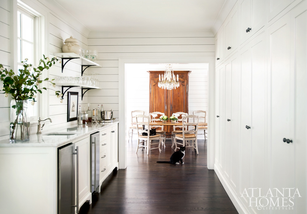 Modern farmhouse style white kitchen with sliplap, open shelves, and black accents