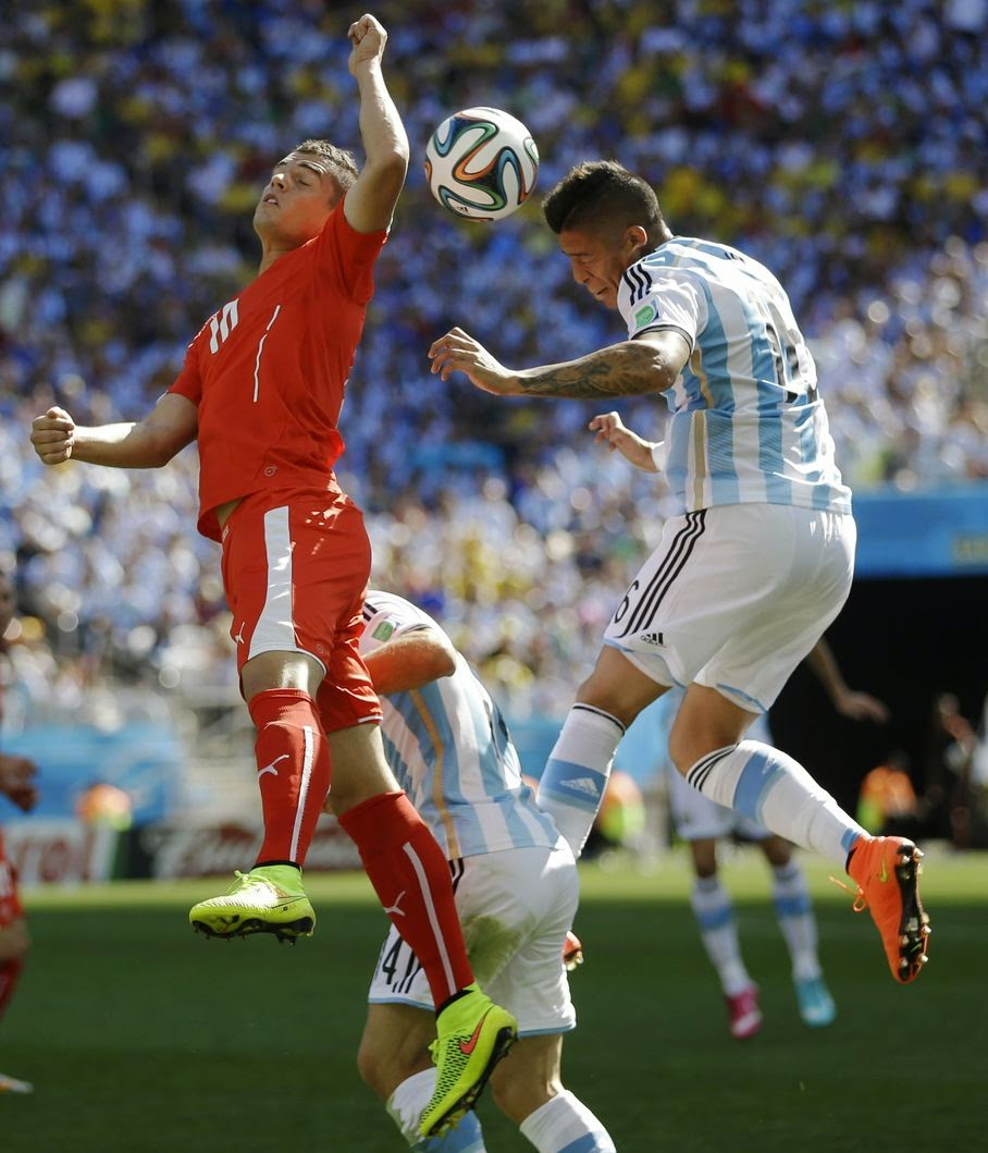 Argentina's Marcos Rojo, right, and Switzerland's Granit Xhaka go for a header during their World Cup round of 16 soccer match at the Itaquerao Stadium in Sao Paulo, Brazil, Tuesday, July 1, 2014.